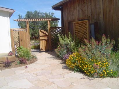 Flagstone patio leading to arbored gate and rustic barn